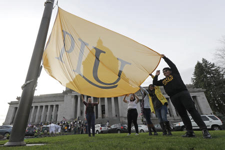 Pacific Lutheran University students raise a PLU flag.