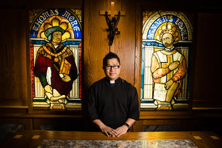 Rev. Bryan Pham stands in front of stained glass windows