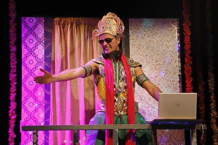 An actor in Indian-style garb performs on stage