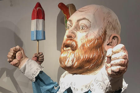 oversized puppet of a bald man with red beard