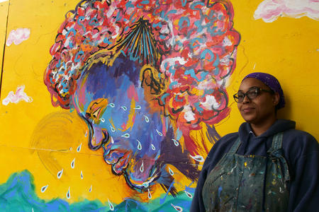 woman stands next to mural