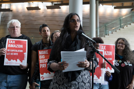 "Councilmember Sawant speaks before supports holding signs reading ""Tax Amazon"""