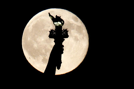 Statue of Liberty torch in front of full moon