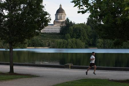 A jogger runs along Capitol Lake with the state Legislative Building in the background