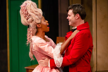a man in a red waistcoat and a woman in a tall pink wig