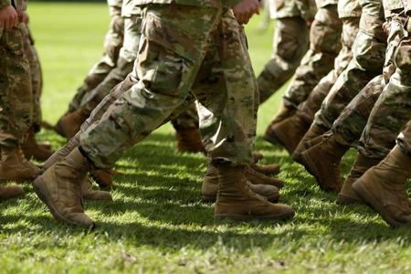 The boots of service members are shown as they march in unison.