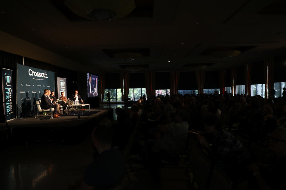 A panel of experts discuss climate change before a large audience.