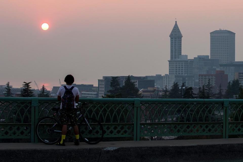 A man stands on the Jose Rizal Bridge in Seattle and looks out at a smoky sunset caused by wildfires in British Columbia