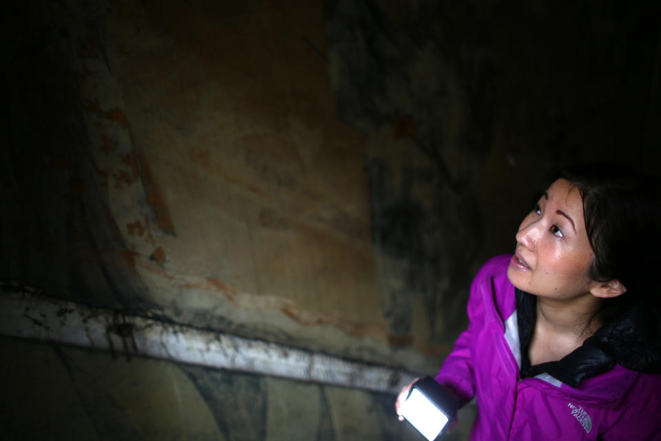 Tanya Woo checks out old murals lining a staircase that used to lead to a 1920s-era jazz club in Seattle.