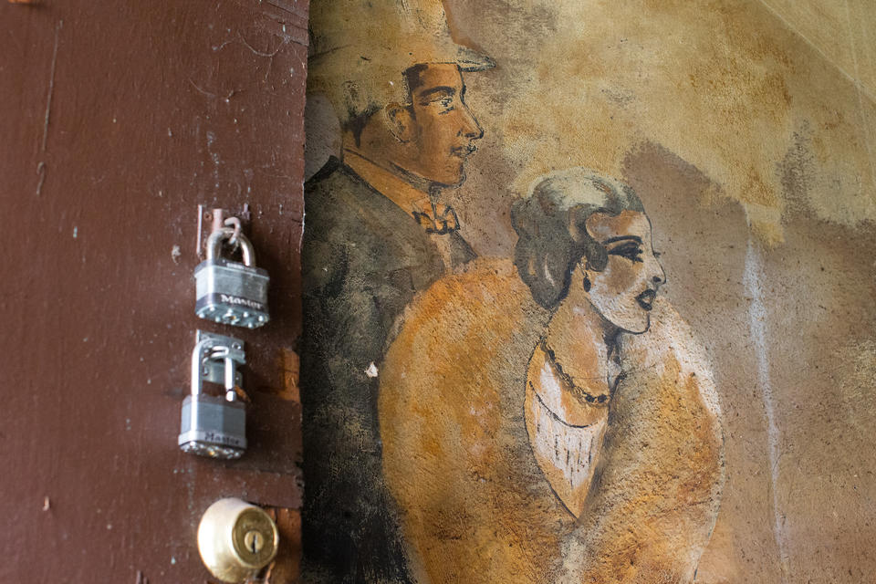 An old mural of a man and a woman is pictured next too a door with padlocks on it.