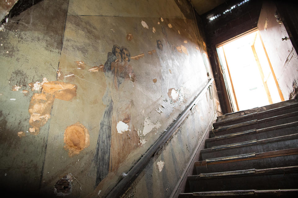 A view looking up the Louisa Hotel staircase where old murals line the walls