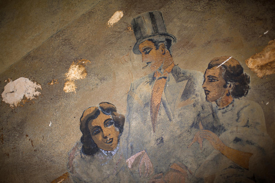 Two women flank a man in a top hat in one of the 1920s murals that line a staircase inside the Louisa Hotel in Seattle's Chinatown International District.
