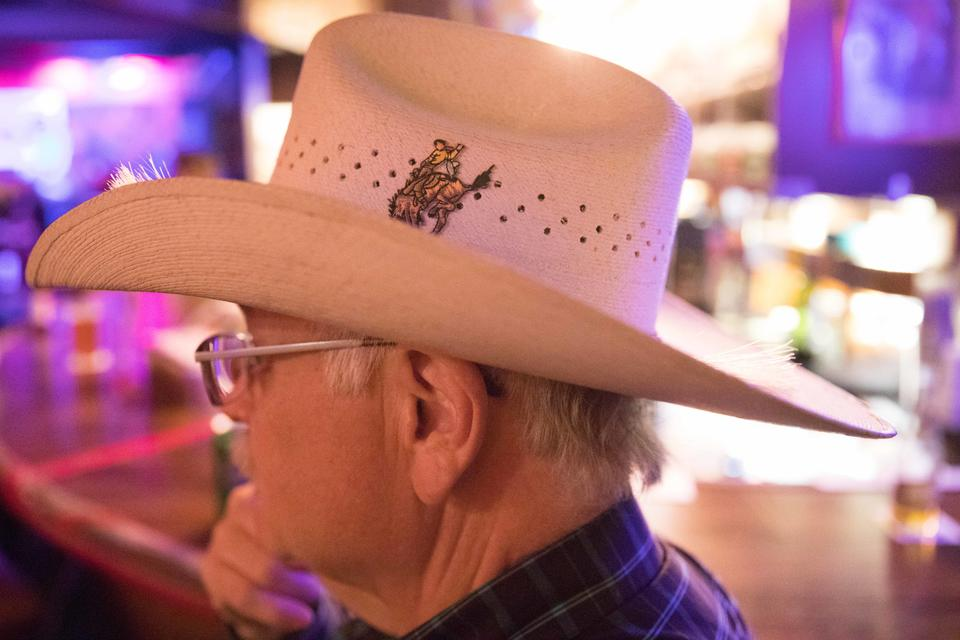 Jim Carden, a regular who has been visiting the bar for decades, sits on a barstool wearing his cowboy hat and watches dancers on the floor at Little Red Hen.