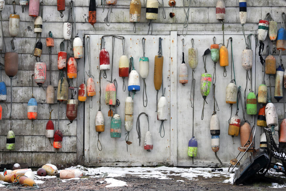 A collection of buoys are seen hanging from a garage near Astoria.