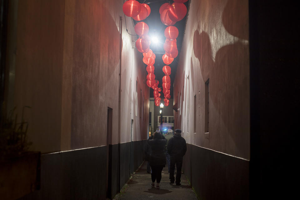 People walk through a decorated alley near Fort George Brewing during Fisher Poets Gathering in Astoria.