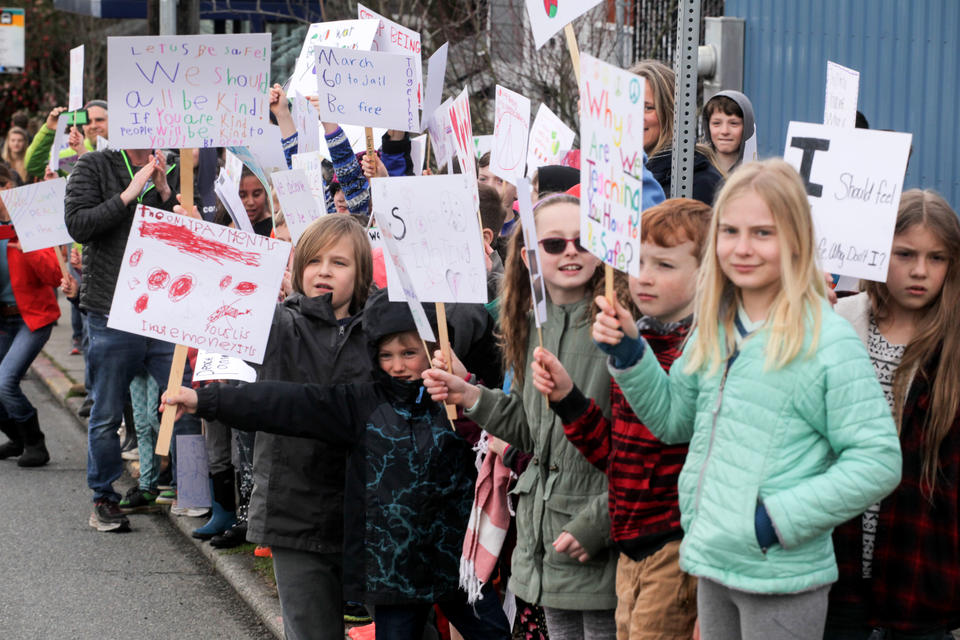 University Cooperative School (K-5) cheer on the high school students as they march from Roosevelt High School to University of Washington