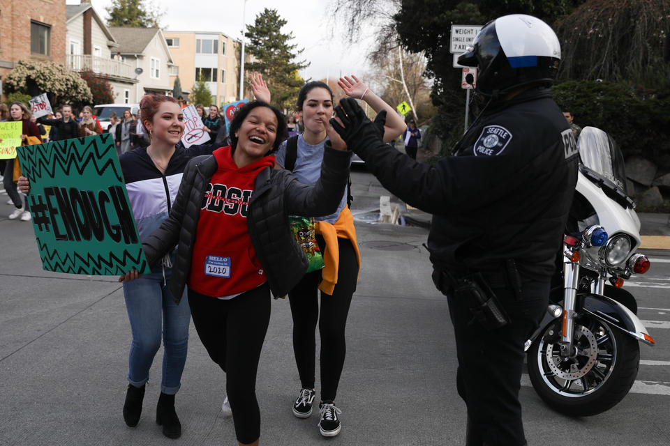 Students give an SPD officer a high-five while marching from Roosevelt High School to University of Washington's Red Square