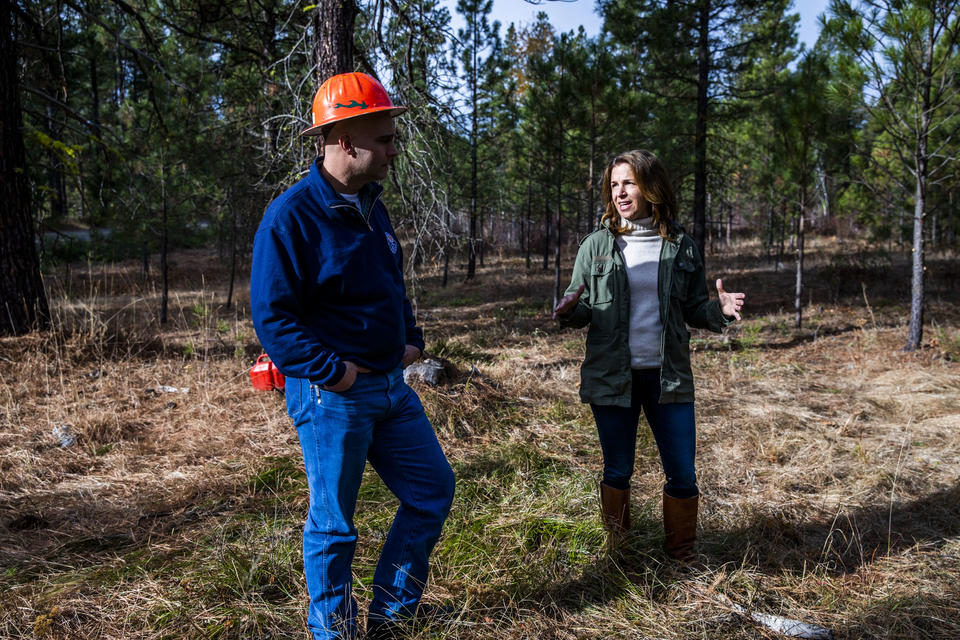 Washington State Lands Commissioner Hilary Franz, right, and Assistant Regional Manager of state lands Larry Leach in the Teanaway Community Forest on Wednesday, Oct. 24, 2018. The Department of Natural Resources is implementing a forest health treatment plan which uses dying forest for cross laminated timber. Franz says this plan will also help keep the cost of wildfire suppression down and make forests more resilient to wildfires. (Photo by Dorothy Edwards/Crosscut)