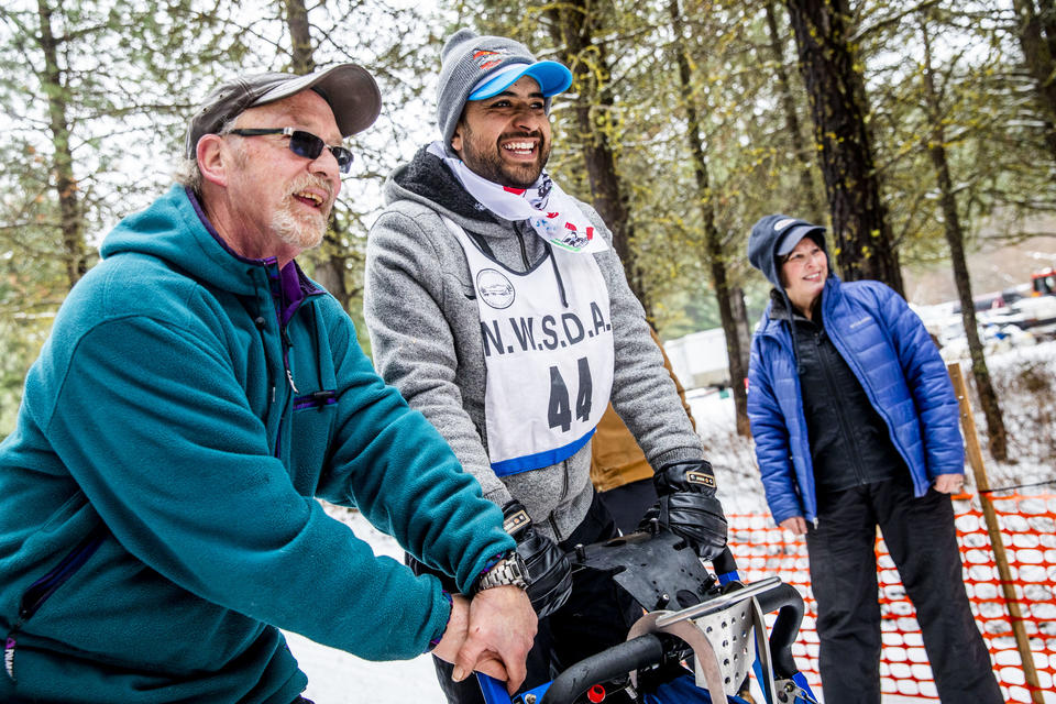 Larry Roxby, left, helps Marcos Padilla get lined up at the start line before his race in the Northwest Sled Dog Association Dogtown Winter Derby at Camp Koinonia in Cle Elum on Saturday, Jan. 12, 2019. Padilla and two other dog sledders from Urban Mushing Leon in Mexico traveled to Washington to work with the Roxby family and their dogs and compete for the first time on snow. (Photo by Dorothy Edwards/Crosscut)