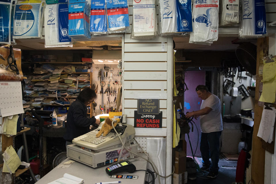 Employee Ogie Estrella and co-owner Guy McNally work on various vacuums at The Vac Shop in Seattle's Georgetown neighborhood, Nov. 16, 2018.