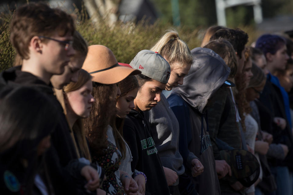 Students stand in a line and link arms for 17 minutes, honoring the 17 killed at a school shooting in Parkland, Florida