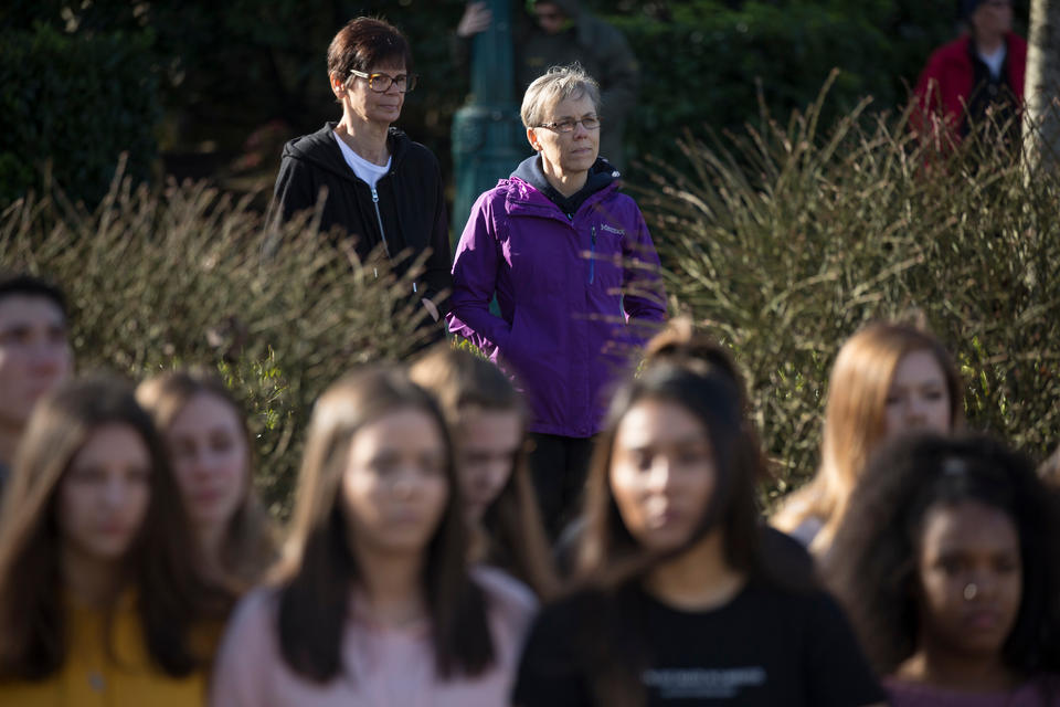 Neighbors Sharon Buren, left, and Cheryl Buren, right join on the sidewalk in front of the school as students link arms for 17 minutes, honoring the 17 killed at a school shooting in Parkland, Florida