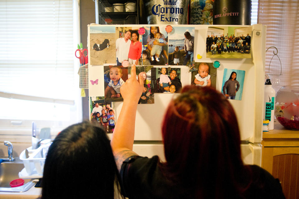 Bopha Khliu, right, looks at pictures of her father, Sun Khliu, with her daughter, Angeliyah Khliu, 13, at their home in Portland.