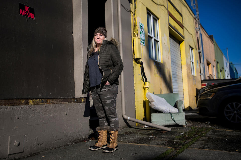 "Jodi Opitz, owner of Seattle Rehearsal, stands for a portrait in front of a ""no parking"" sign she keeps up on her building to make sure her business is accessible to herself and her customers 24/7 on Occidental Avenue South in Seattle's SODO neighborhood"