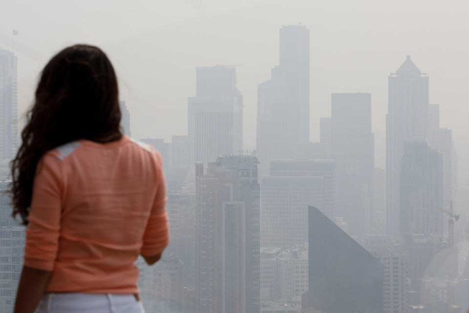 A woman looks at the skyline from the Space Needle observation deck on Monday, Aug. 20, 2018 in Seattle. Haze from wildfires caused a decrease in air quality in the area. (Photo by Sarah Hoffman/Crosscut)