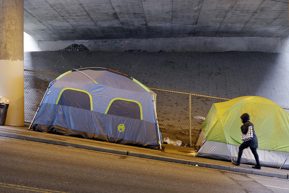 Tents are shown on a sidewalk under an overpass