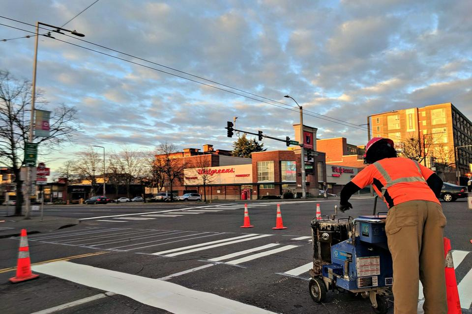 A Seattle Department of Transportation worker repairs a crosswalk at a main intersection in Ballard