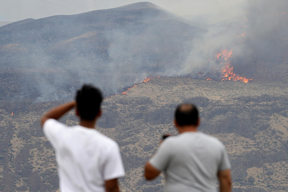 Two onlookers see a wildfire on a hillside near Vantage, Washington.