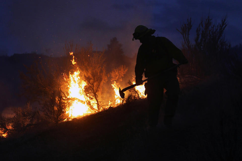 In this photo taken on Friday evening, Aug. 21, 2015, Gold Bar fire Lt. Scott Coulson investigates brush fires in the hills outside of Omak,  Wash., as wildfires continue to burn throughout north-central Washington.  (Genna Martin/The Herald via AP)