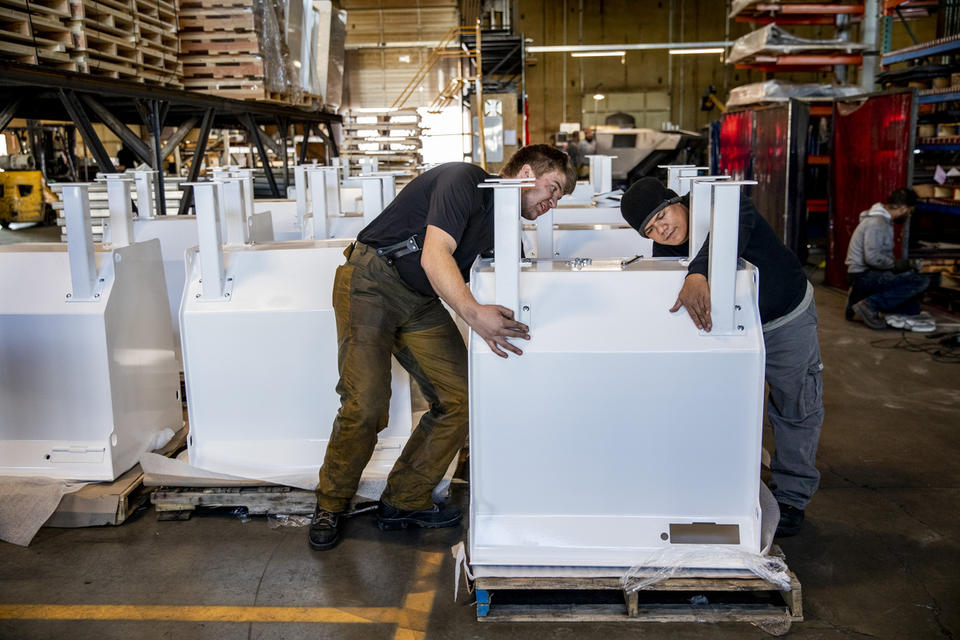 Two workers put together white steel pieces that form a ballot dropbox.