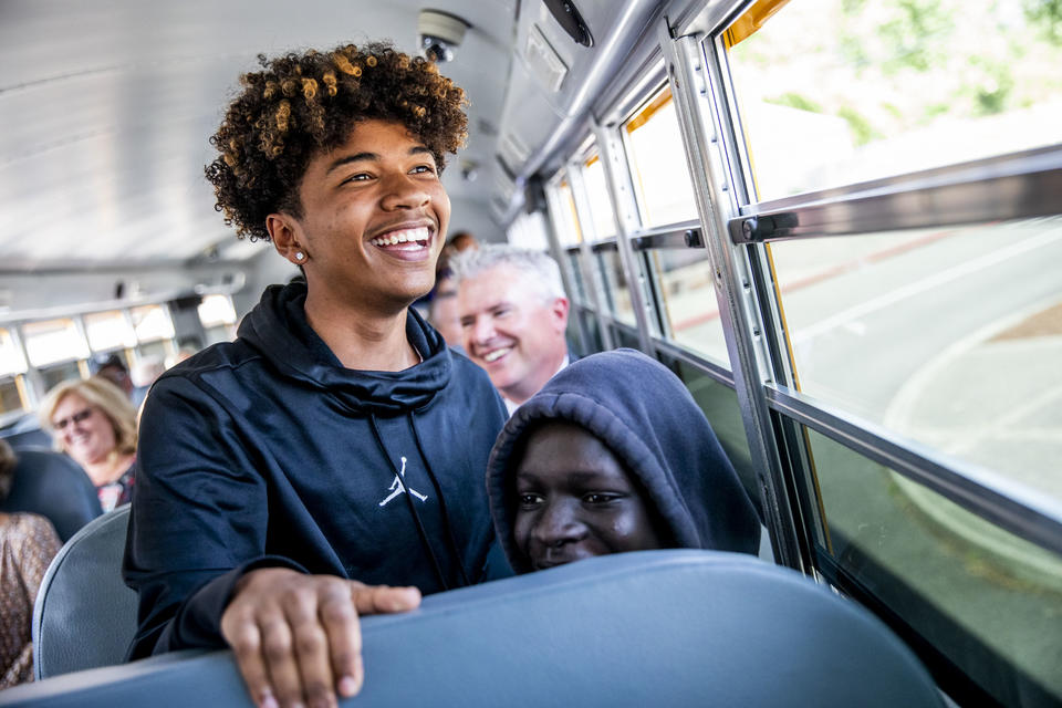 "Freshmen Malik Goodrum, left, and Modi Wani ride the first electric school bus in Washington state during an event with Governor Jay Inslee at Franklin Pierce High School in Tacoma on June 17, 2019. ""I feel pretty privileged to be on this bus with Governor Inslee right now,"" Goodrum says. (Photo by Dorothy Edwards/Crosscut)"