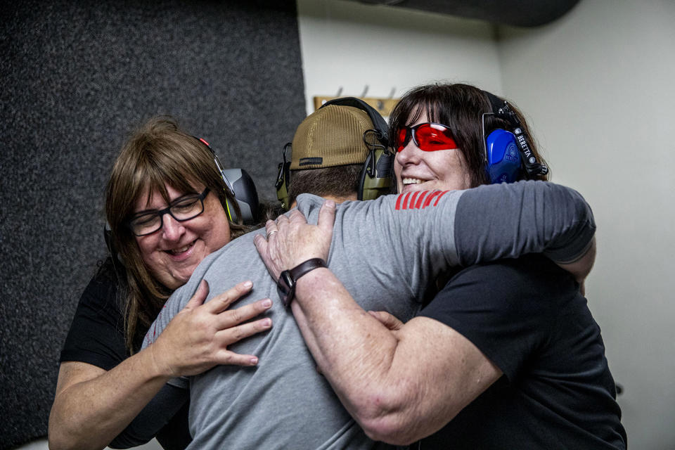 "Jan, 62, left, and Melissa Elmer, 68, hug John Abbitt after he taught them how to shoot a gun for the first time at West Coast Armory in Bellevue during a Pink Pistols range meetup on May 18, 2019. The couple recently purchased their first firearm and came to Pink Pistols to learn how to shoot it. ""I'm comfortable with this group of people more than any other group,"" Jan says. (Photo by Dorothy Edwards/Crosscut)"