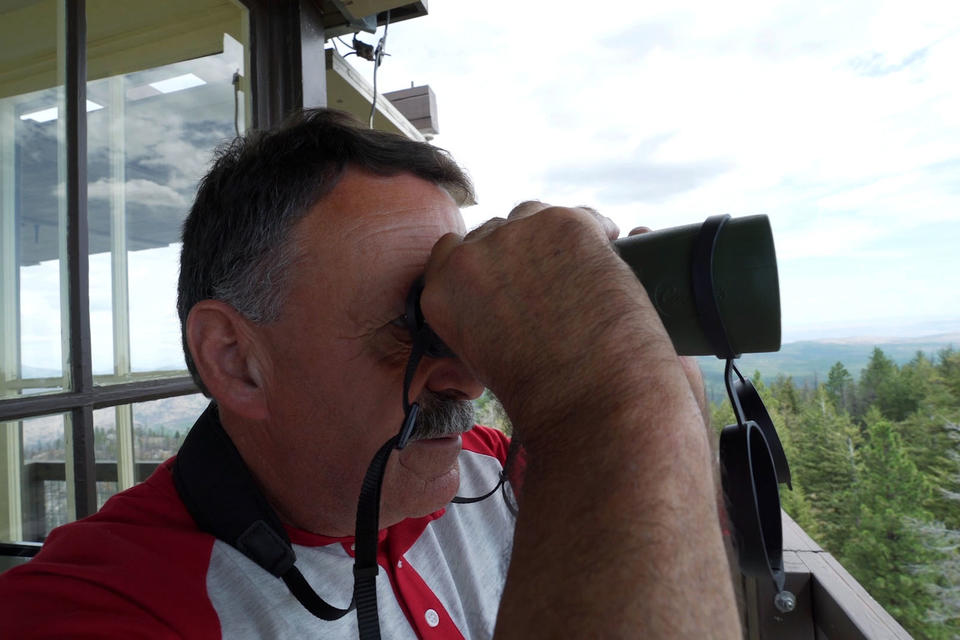 Bill Austin looks through his binoculars.