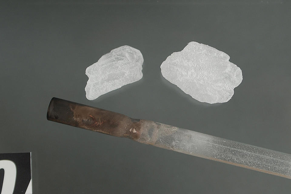 methamphetamine and a pipe sits on a table