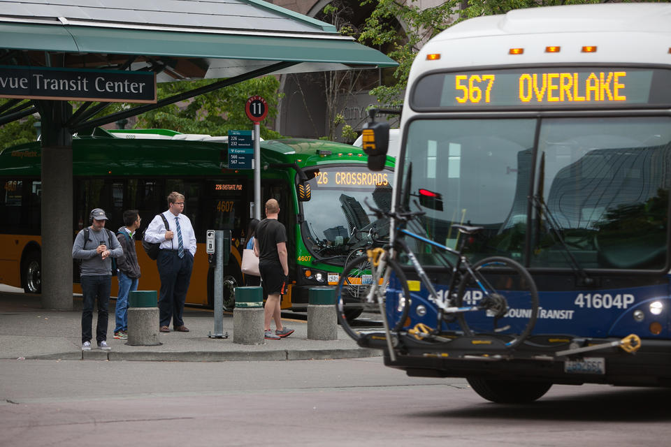 A King County Metro bus stops as a Sound Transit rolls out