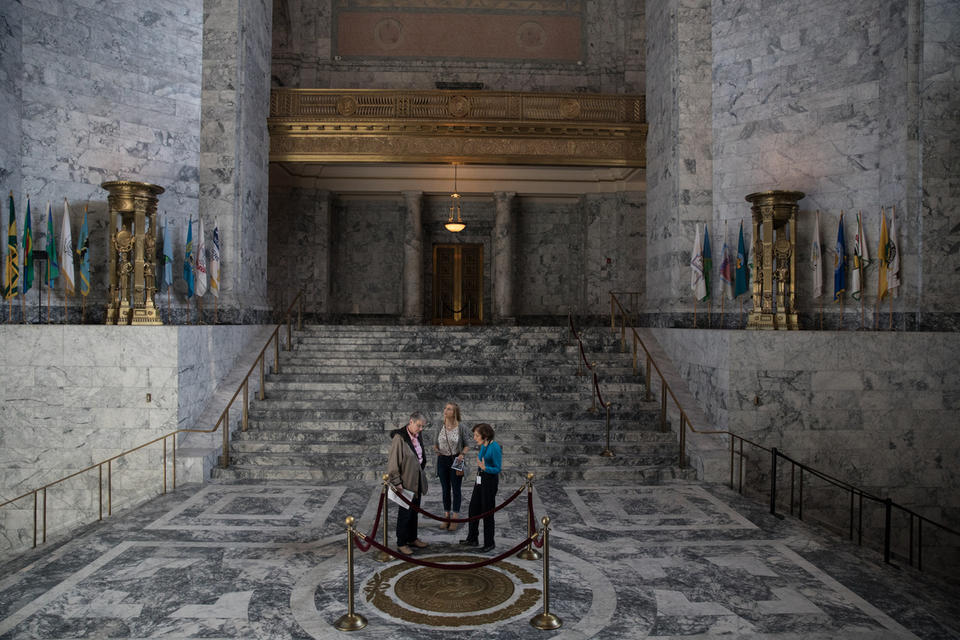 Visitors stand in the rotunda of the state Capitol in Olympia, by a bronze seal of George Washington and surrounded by the Capitol's marble halls.
