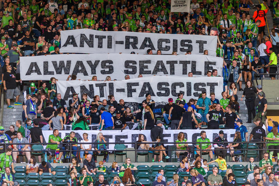 Sounders fans wave anti-racist and anti-fascist banners